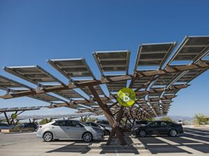 Cars parked under an awning that has solar panels.