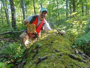Chris Cantway of TNC kneels and poses with a fallen log