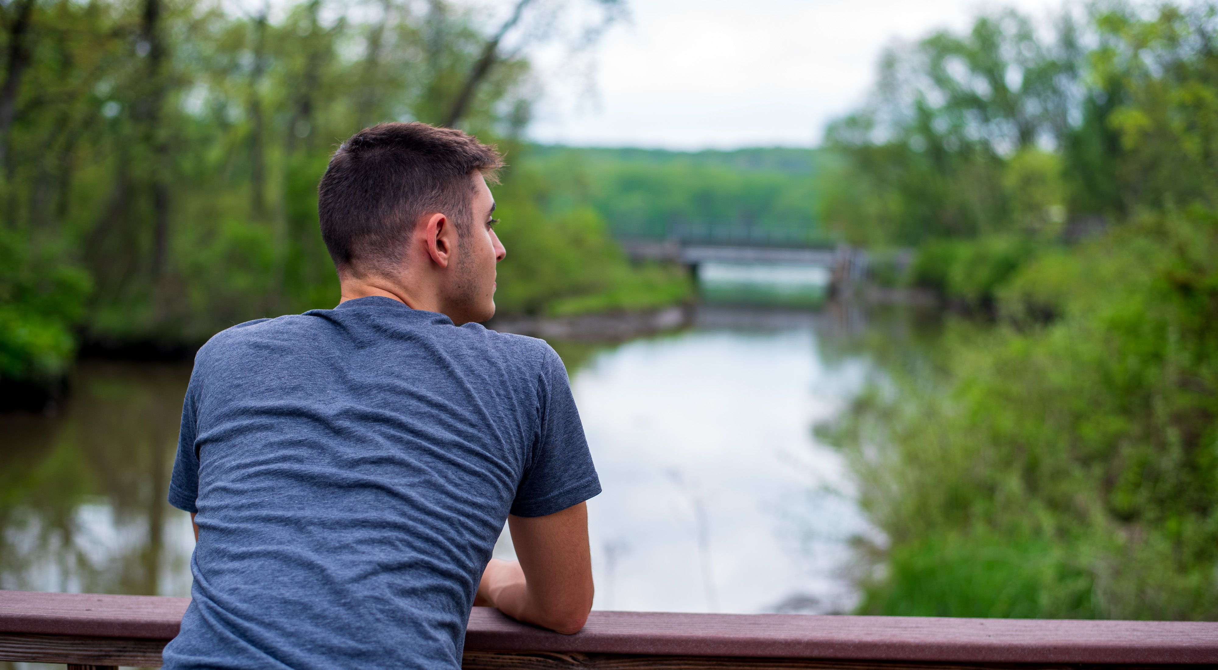 A person leaning on a railing and looking out over a river.