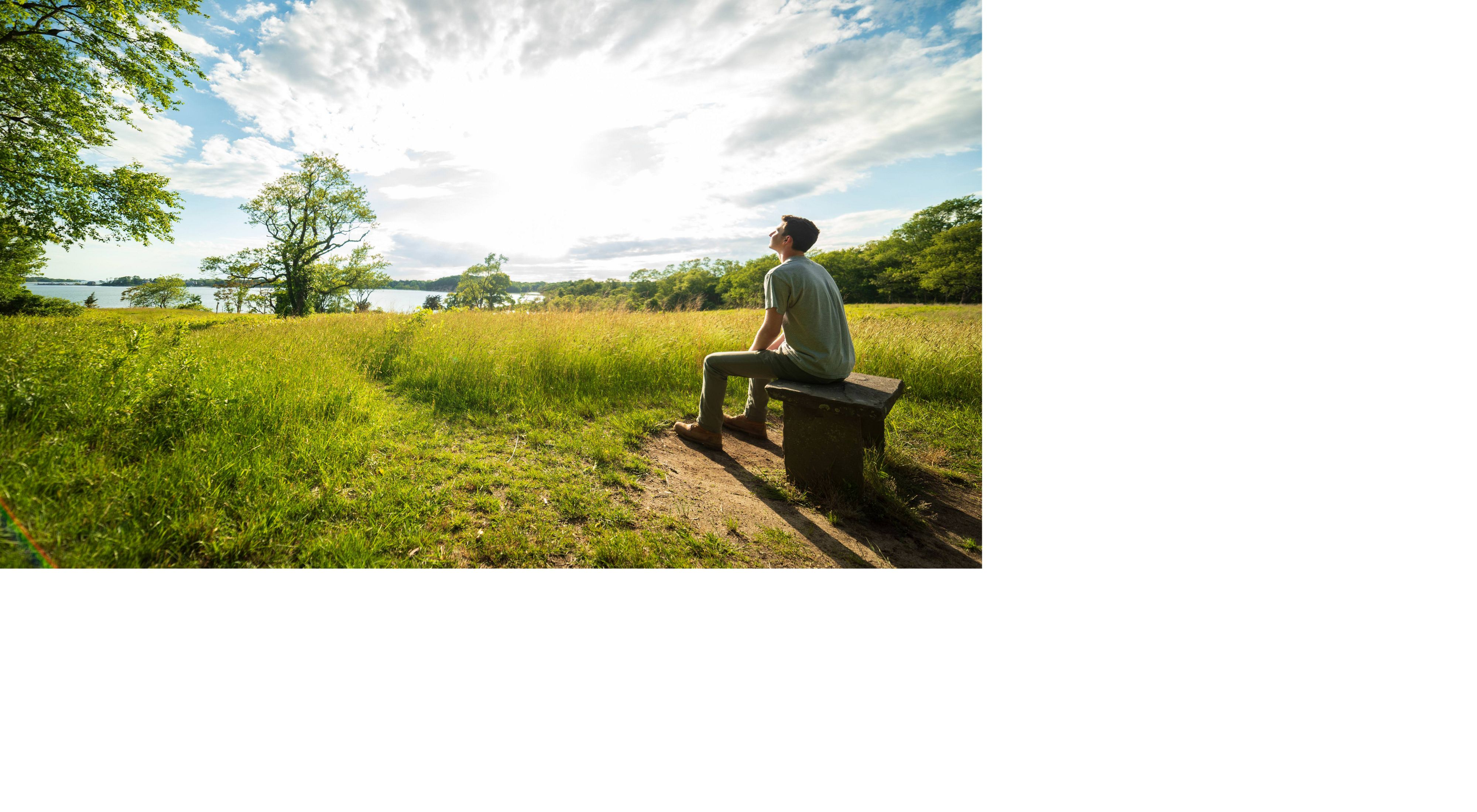 man sitting near a field