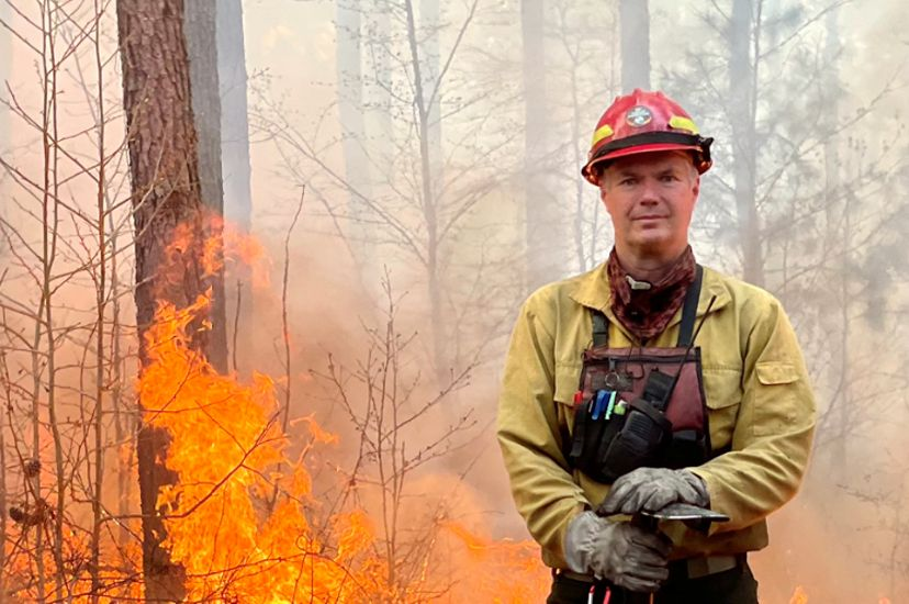 Virginia Stewardship and Fire Program Manager Bobby Clontz poses at the edge of a fire line during a controlled burn. A man wearing yellow fire gear holds a long handled pick ax.