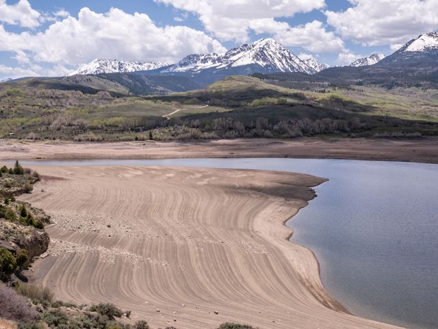 Low water levels in a reservoir expose lines of sediment., with snow-capped mountains in the distance.