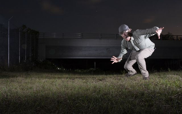 At night, man kneels and raises arms at camera, in front of overpass