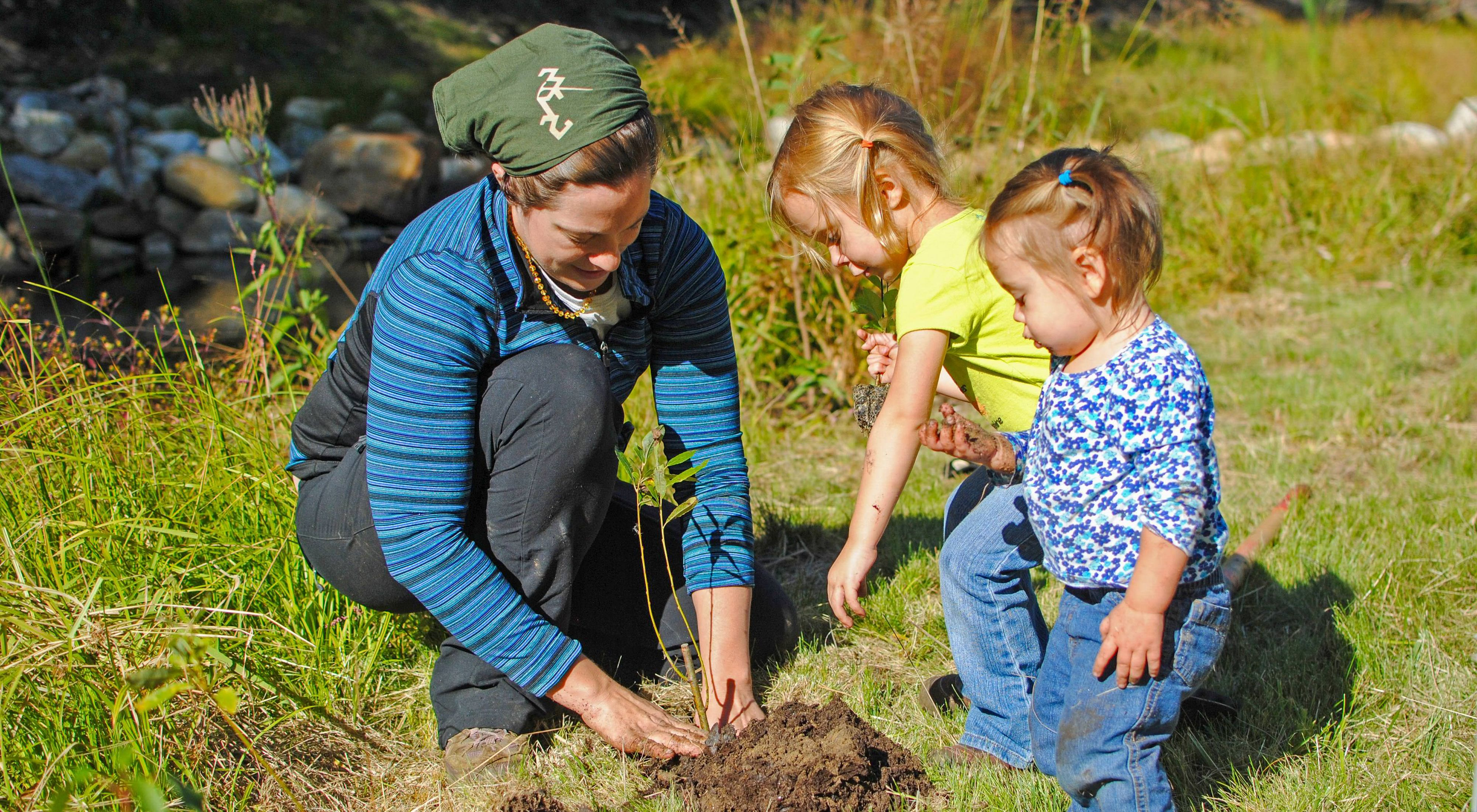 A volunteer plants a tree with help from two young children.