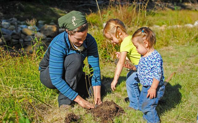 2 toddlers watch as a volunteer plants a plant in a grassy area near a river.
