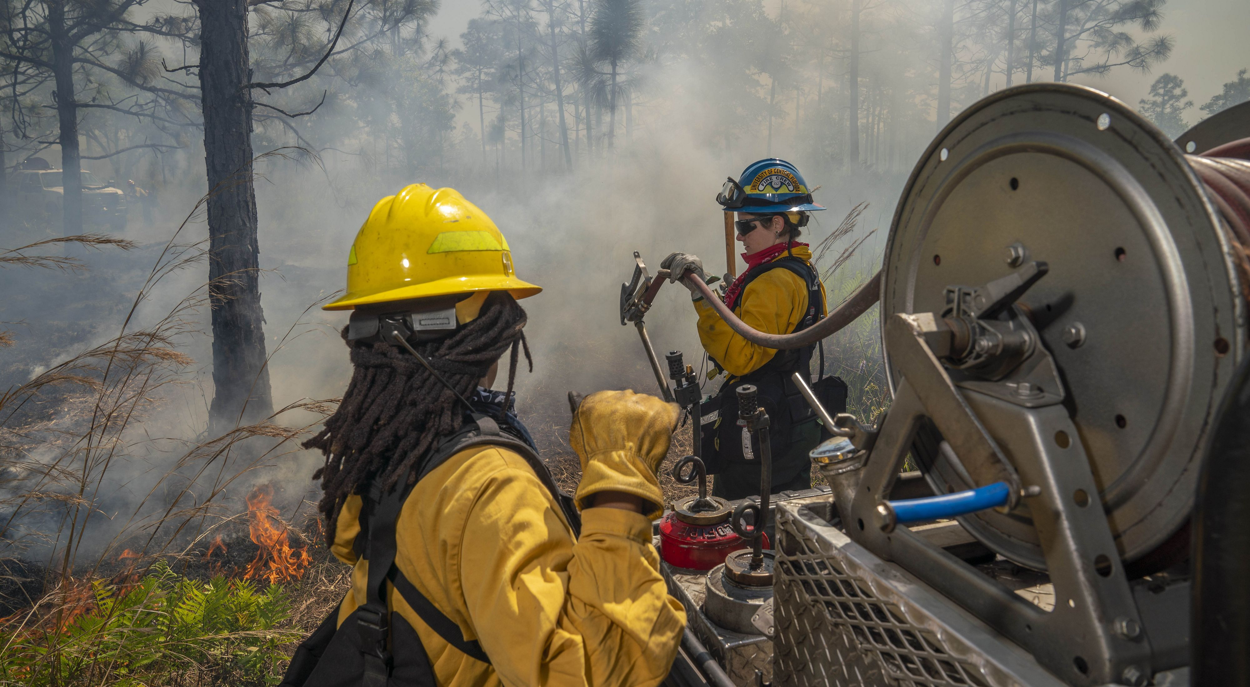 Two wildland fire workers manage a hose reel on a Type 6 engine during a controlled burn in Florida.