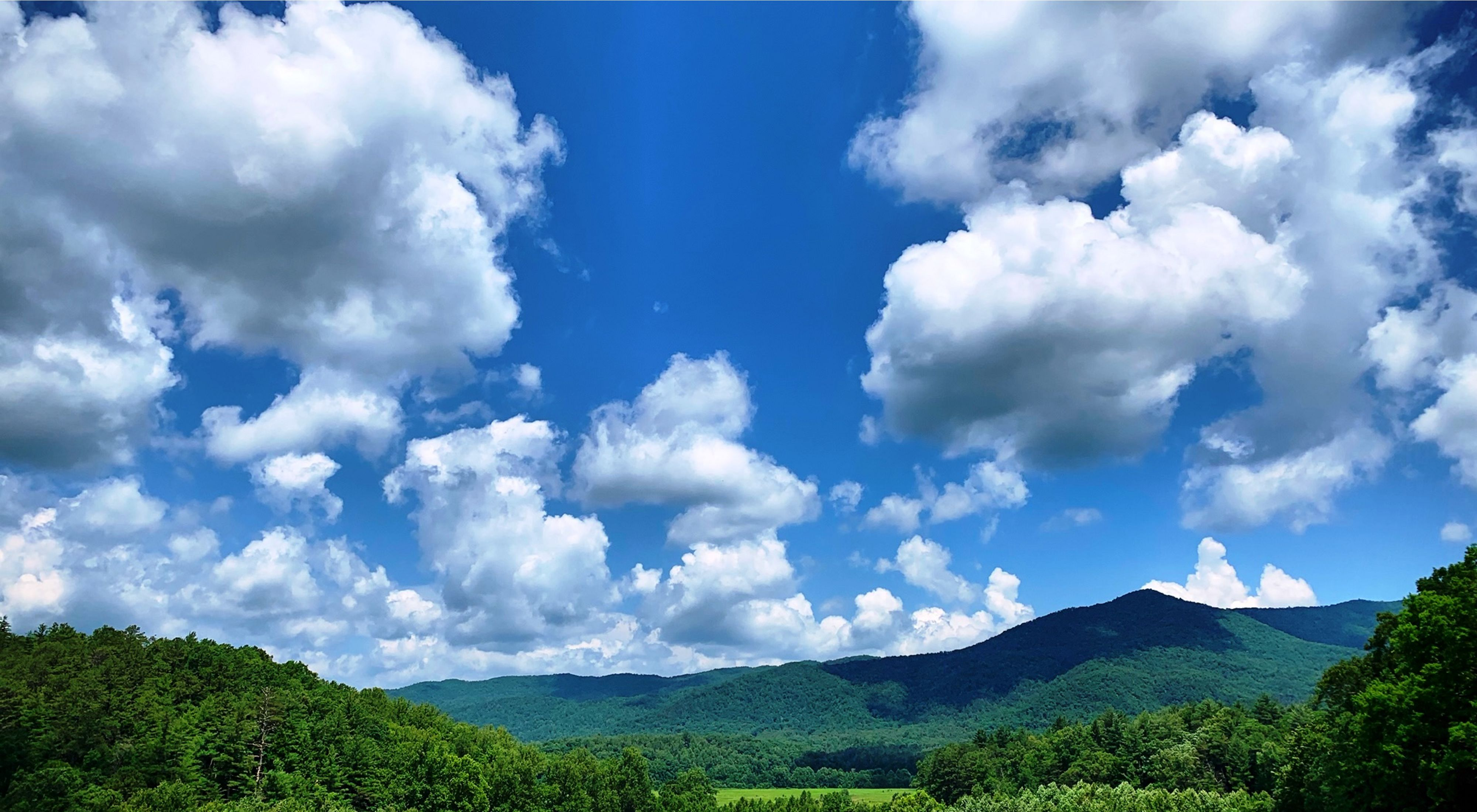 A blue sky and white clouds frame a mountain valley.