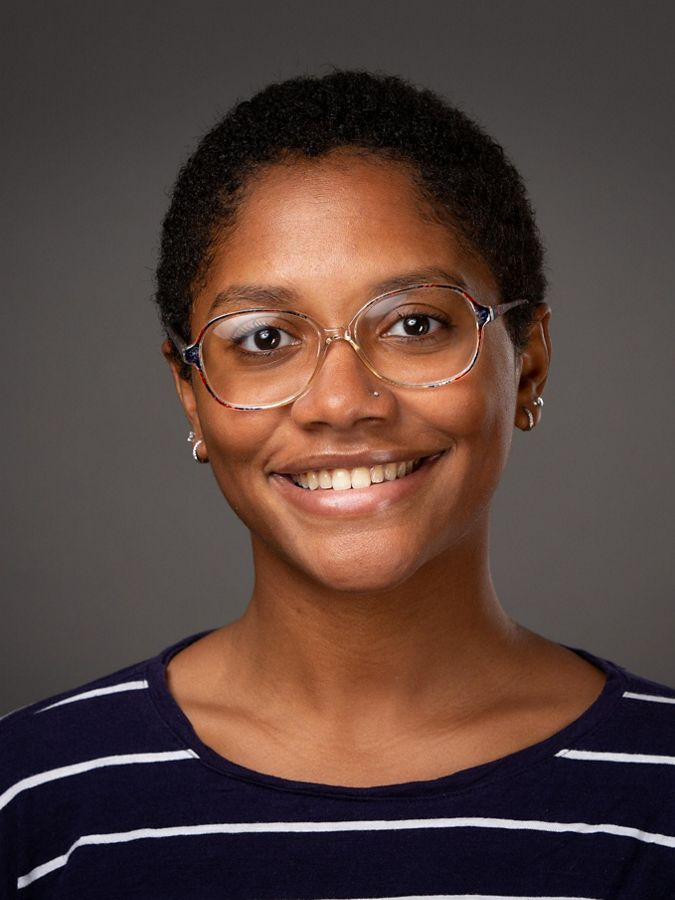 African-American woman in glasses smiling.