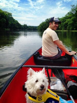 A man paddles a canoe with his white dog in the back.