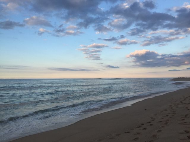 A view of the Atlantic ocean from the beach, with sand in the foreground and a partly cloudy sky at dusk in the background.