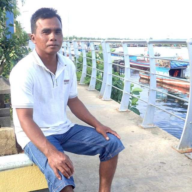An Indonesian man sits on a dock with boats behind him.