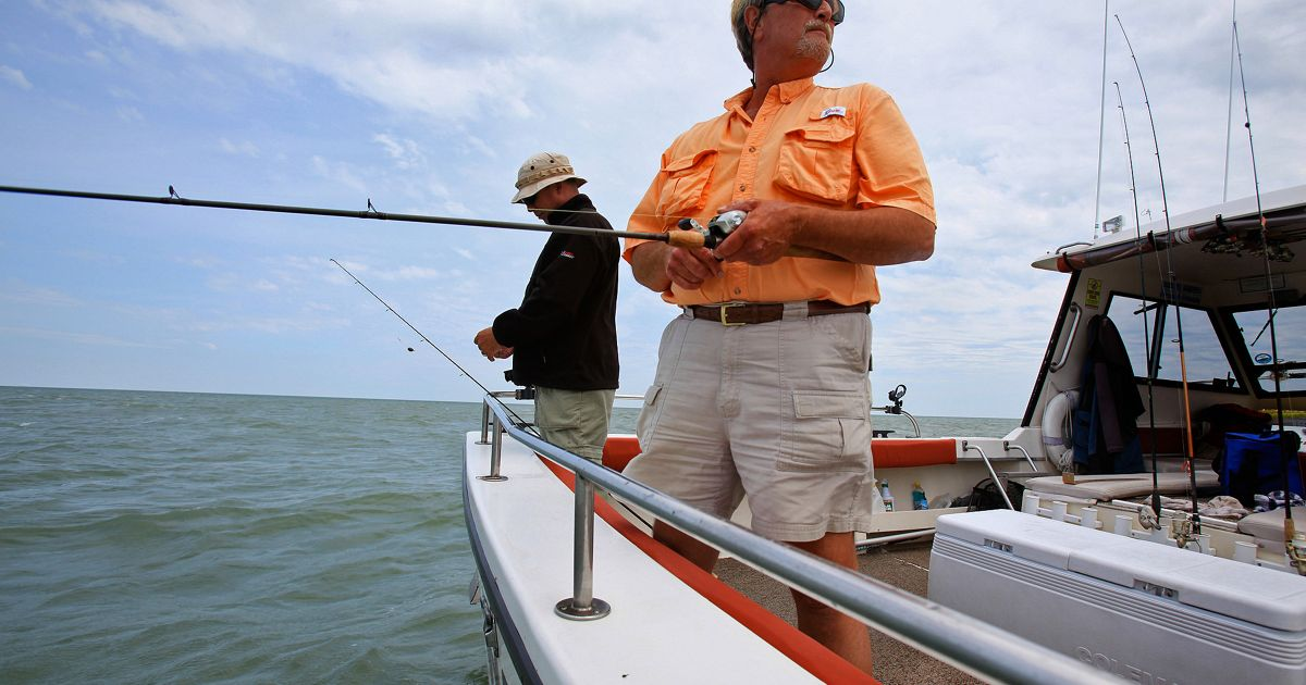 Two men stand on the side of a fishing boat with fishing poles in the water.
