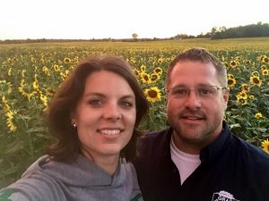Carrie Vollmer-Sanders with husband Ryan at their sunflower field.