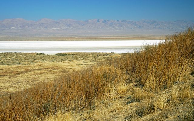 A white expanse of minerals on a dry lakebed with hills in the distance.