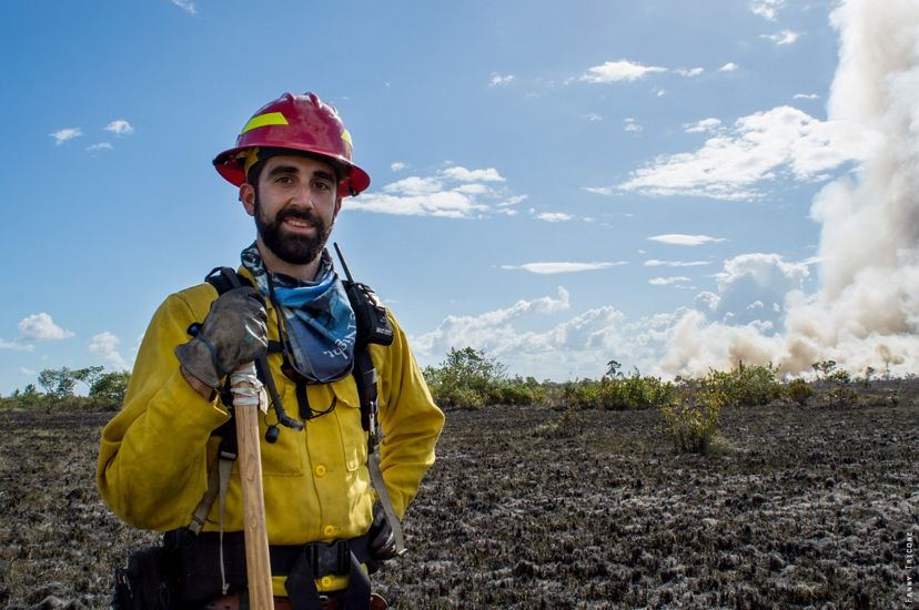 A man wearing yellow protective fire gear and a red hard hat stands in front of an open field that has been burned over.