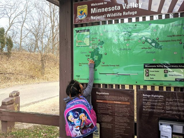 A small child points to a map at the Minnesota Valley National Wildlife Refuge