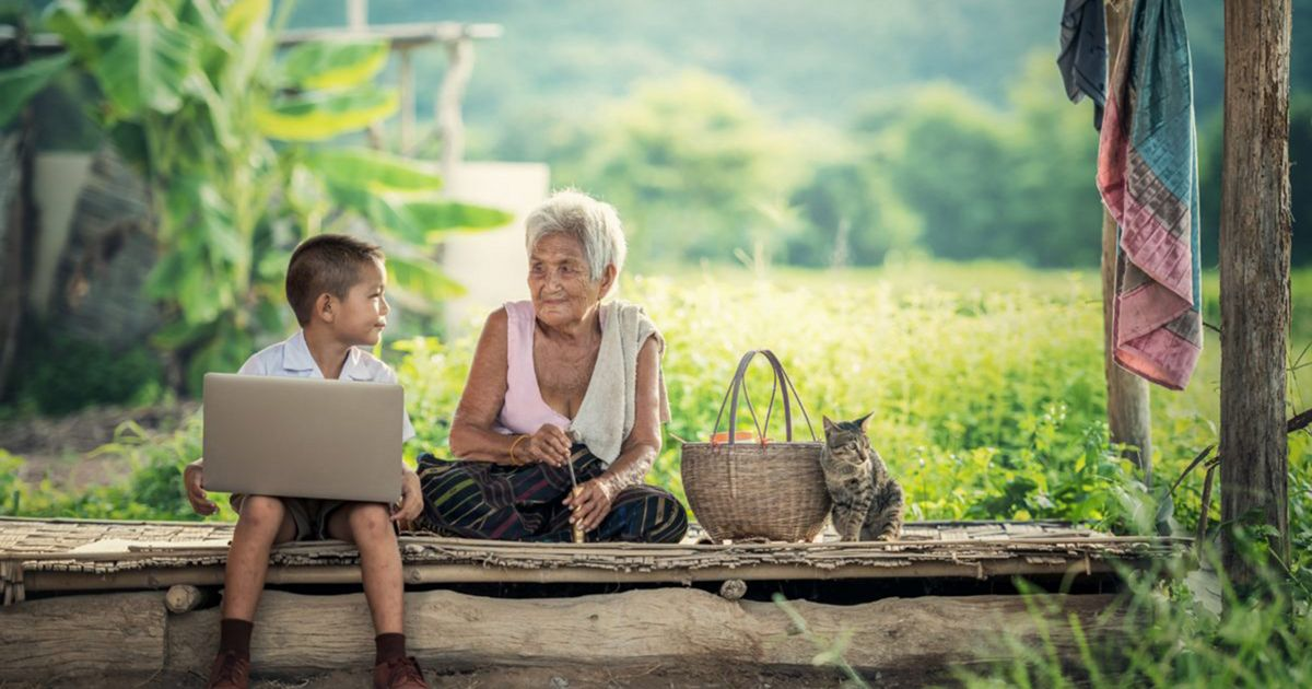 A young boy holds his computer next to an older woman a