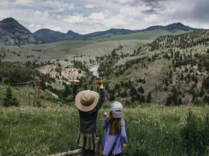 Photo of two children in foreground, sweeping views of Yellowstone National Park in background.