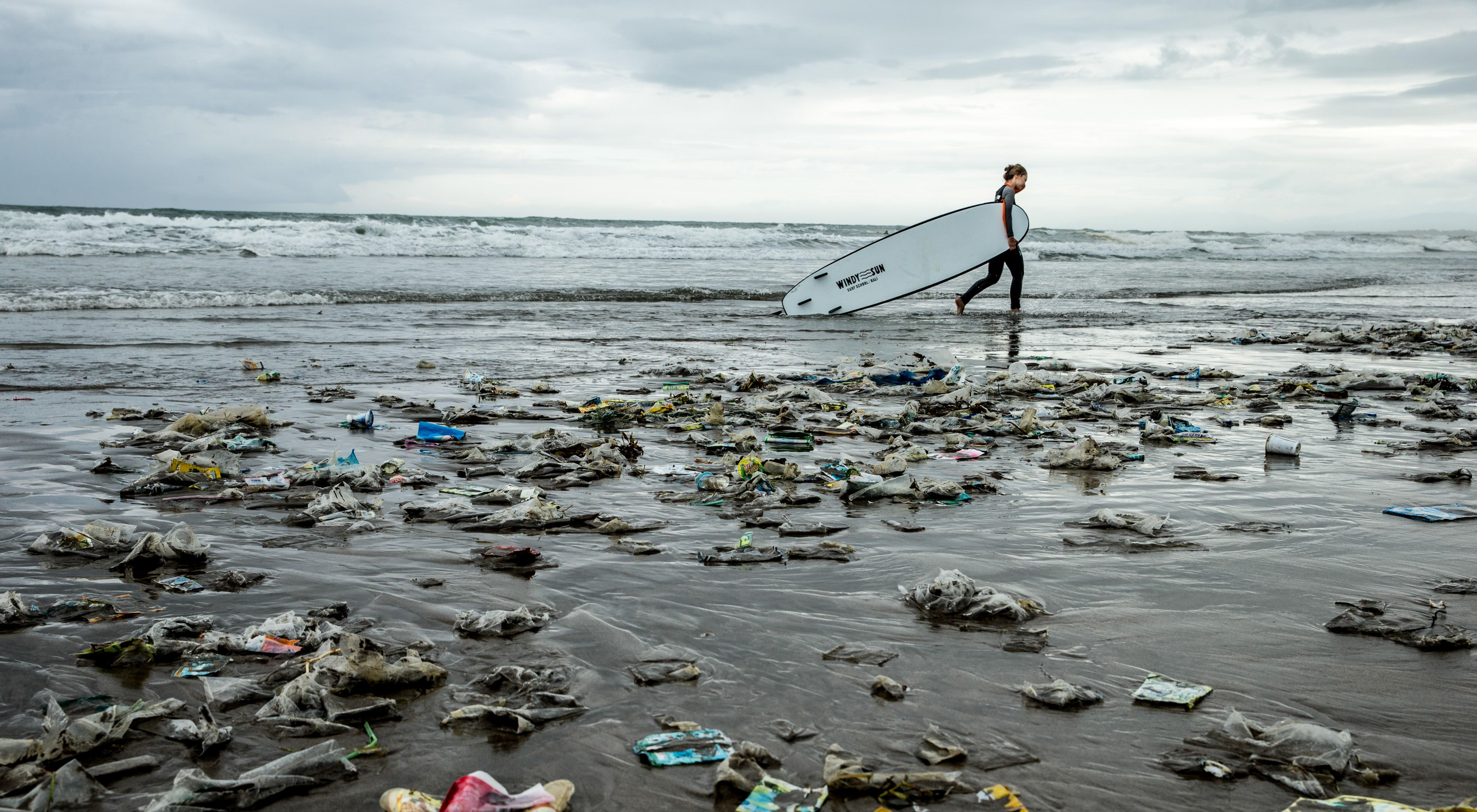 A surfer walks on Kuta Beach, Bali, Indonesia during the monsoon season, when onshore winds bring large amounts of trash to the shores of Bali's west coast.