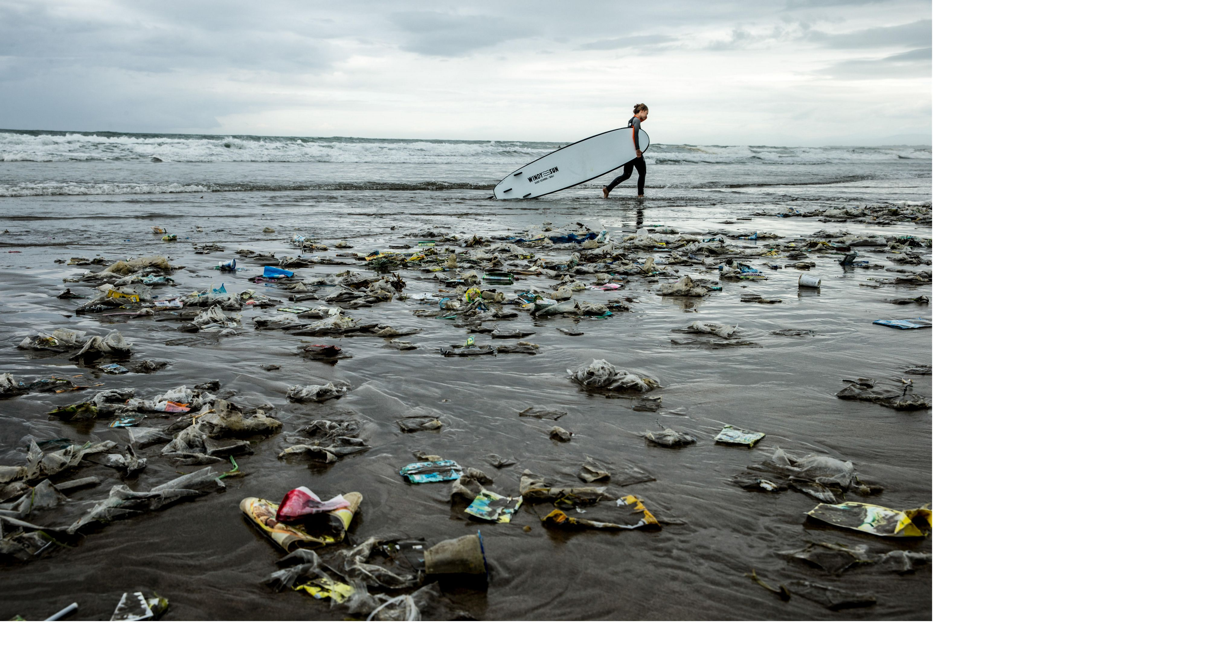 A surfer walks along the shore of a beach carrying a surf board, with large amounts of trash strewn on the sand in the foreground.