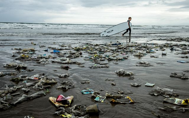 A surfer walks on a beach covered in trash.