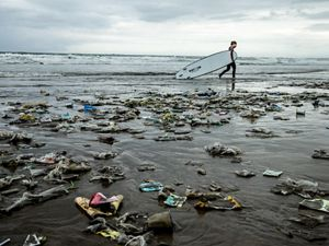 Surfer walking past garbage strewn on a beach.