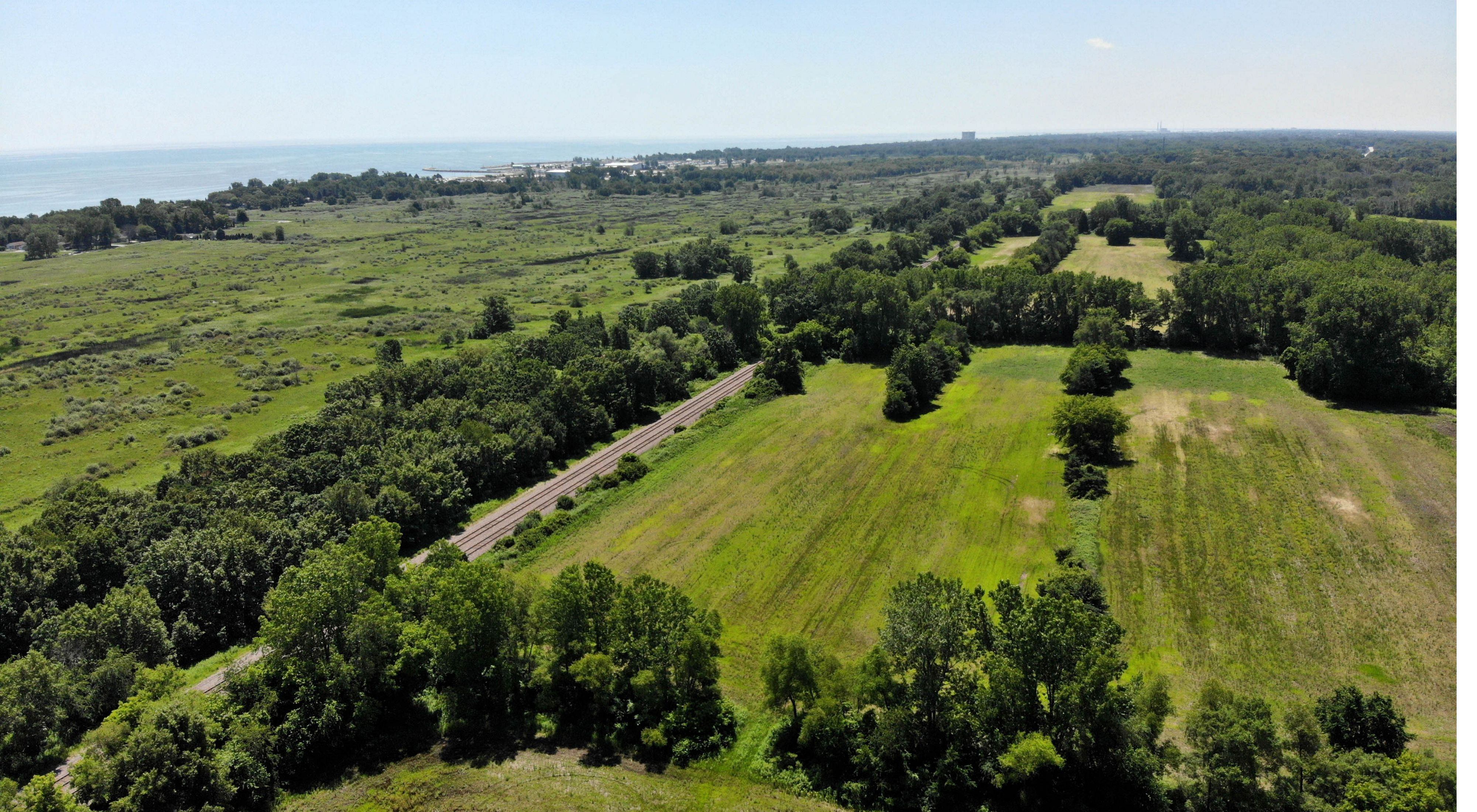 Aerial photo showing the restoration area in the foreground with open land and trees, the Chiwaukee Prairie wetlands beyond that and Lake Michigan in the distance