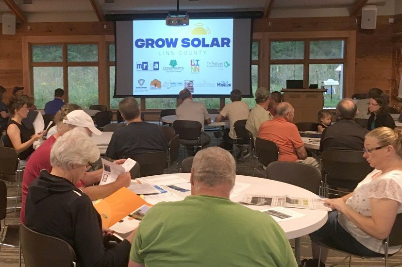 Photo of people sitting at tables during a presentation about solar electricity in Iowa.