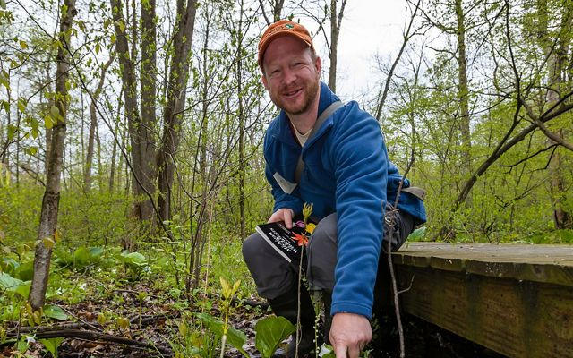 Restoration Director Chris May points out plants for hikers at Nan Weston Nature Preserve at Sharon Hollow.
