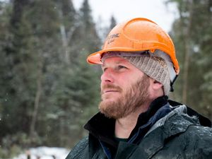 Close up of Chris Stone in the woods wearing his hard hat.