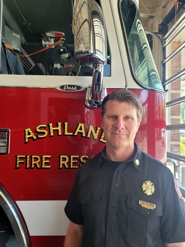 Photo of Chris Chambers standing in front of an Ashland, Oregon, fire truck.