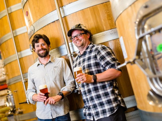 Two men drink beer at a brewery.