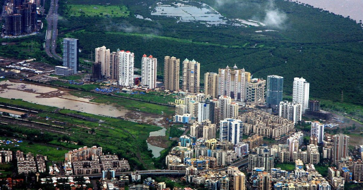 City buildings surrounded by forest.