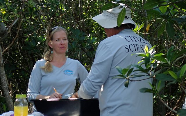 Two volunteers stand at a table outside surrounded by foliage.