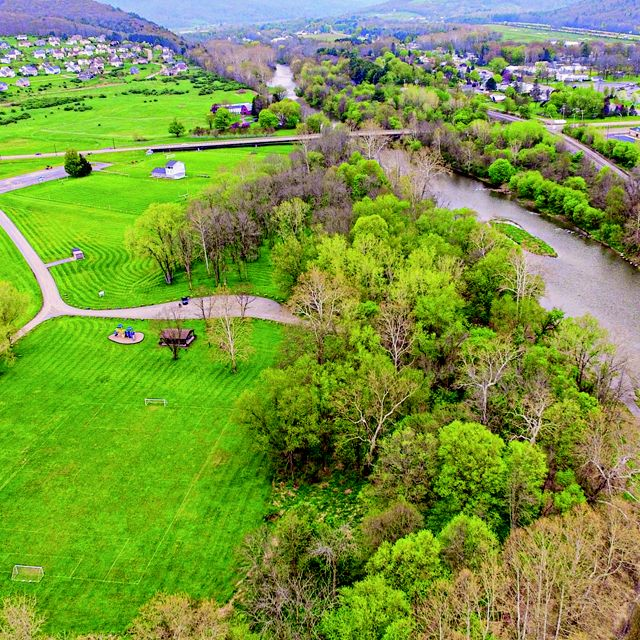 Aerial view of valley studded with green grass and shrubbery on lefthand side, a river cutting down the middle to righthand side, and green and orange shrubbery and homes on the righthand side.