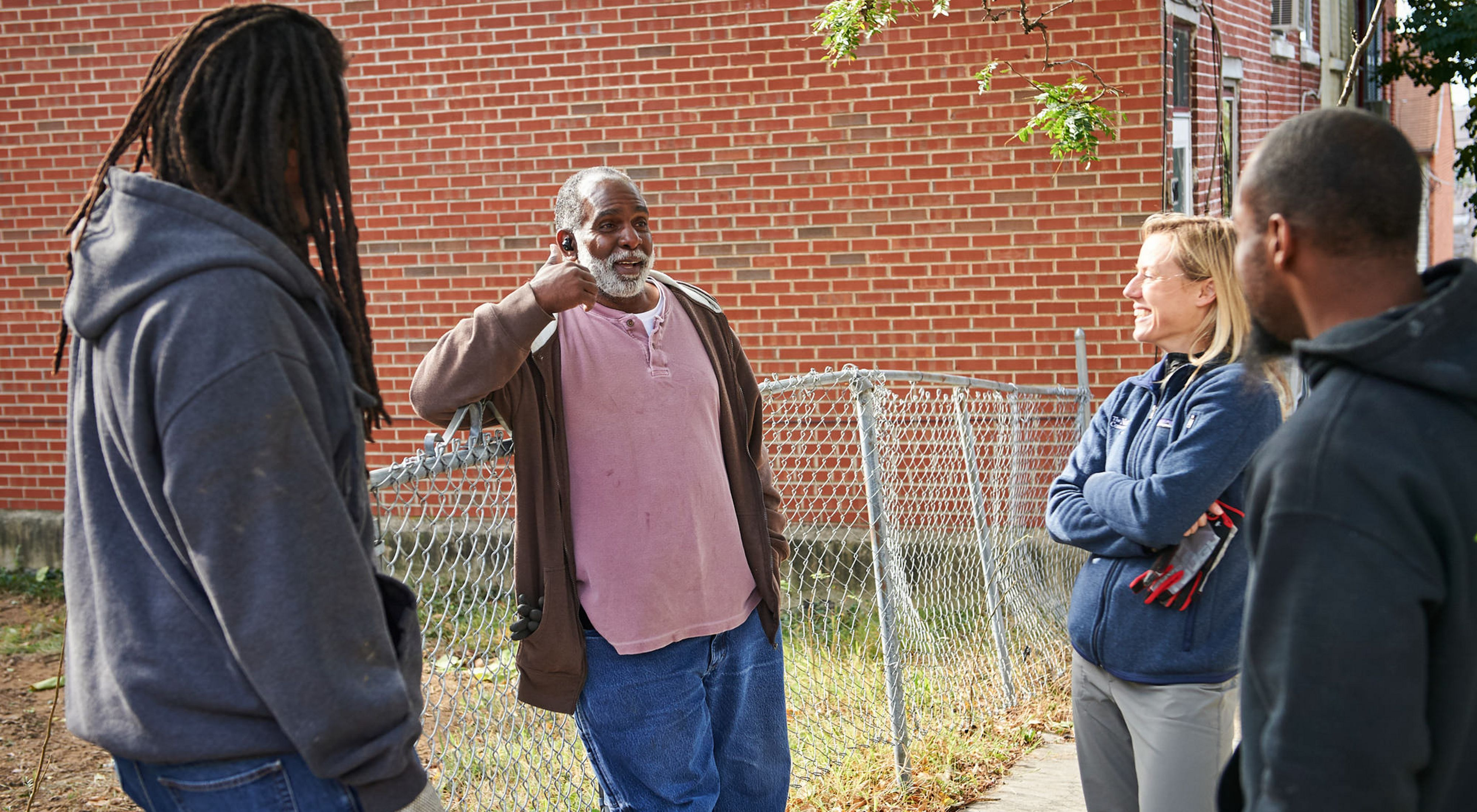 Four people stand together talking next to an open lot. The man in the center is the focus of attention. He is smiling and gesturing as he talks.