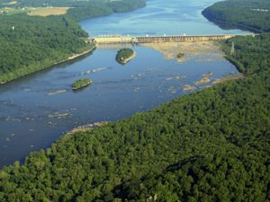 Aerial view of the Conowingo Dam dividing the Susquehanna River in two. The river is bracketed on either side by a thick green forest.
