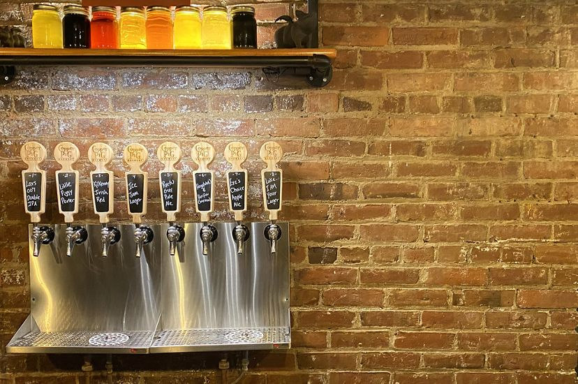 A row of 8 metal taps hang on a brick wall at The Copper Pig Brewery in Lancaster, New Hampshire.