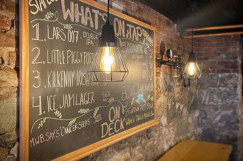 A chalkboard on a brick wall outlines what's on tap at the Copper Pig Brewery.