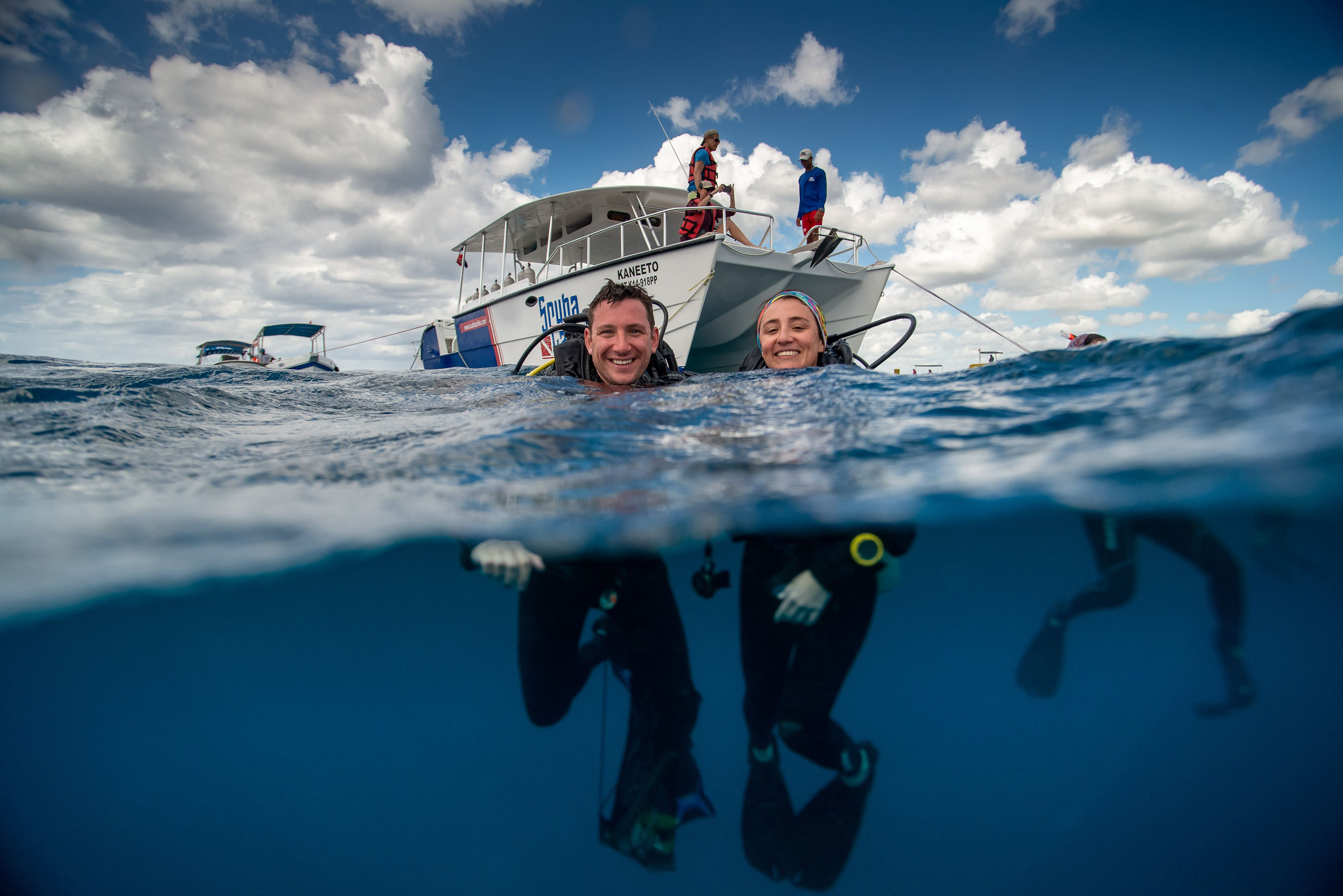 a man and woman in diving gear float in the water