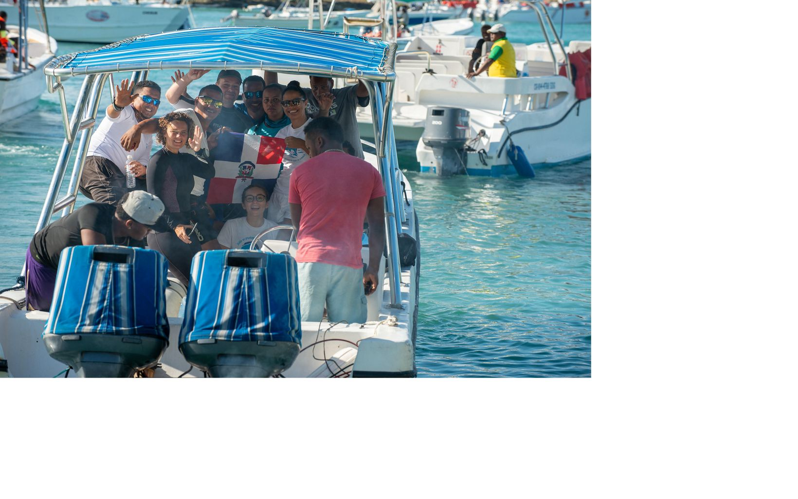 Rita Sellares, in her black wetsuit, and crew of divers wave goodbye as they set off to dive.