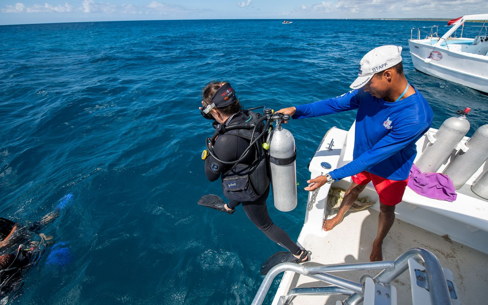 A diver steps off a boat in the Caribbean Sea as part of a coral restoration project off the coast of the Dominican Republic.