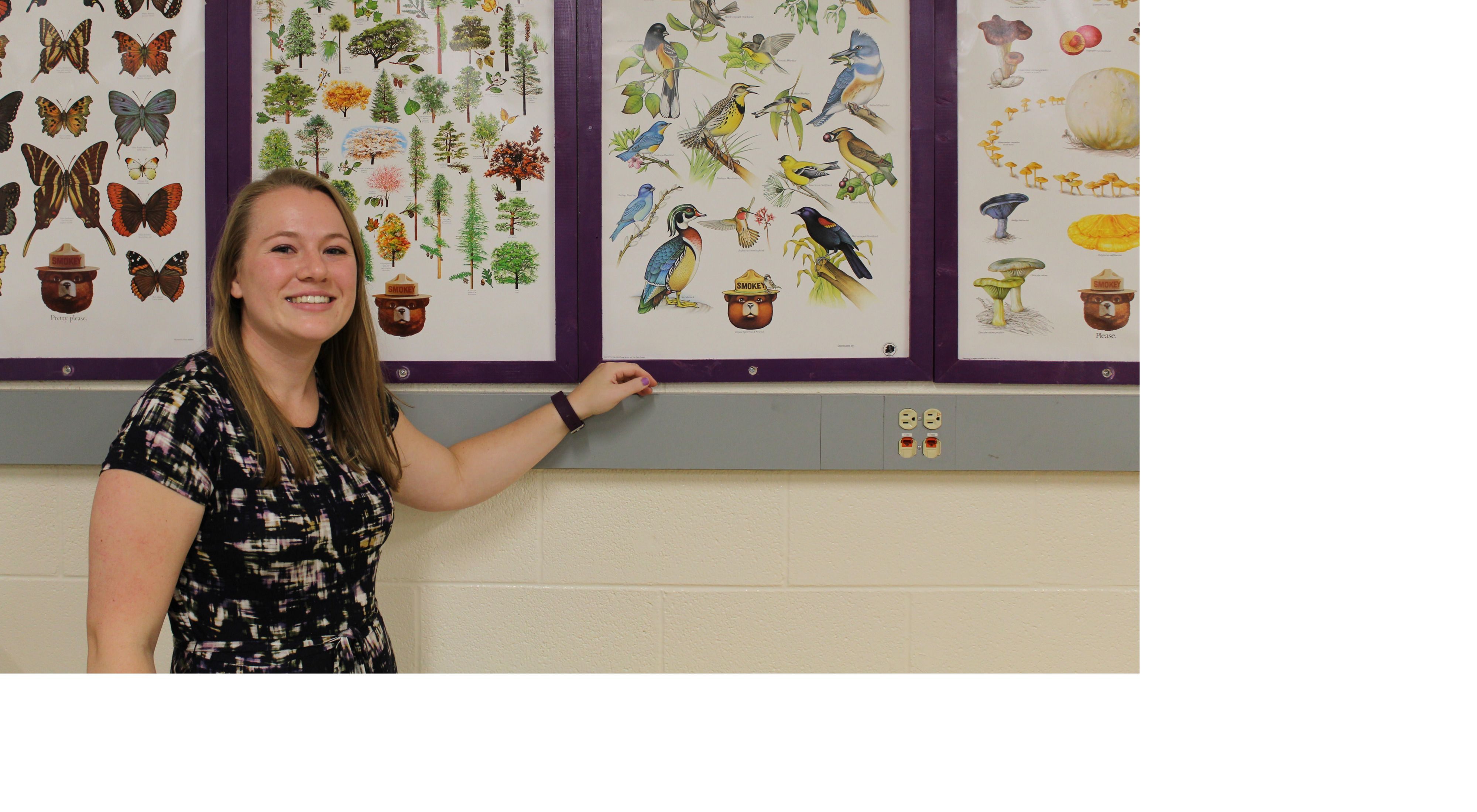 Close-up of Wisconsin teacher Corinne Grossmeier standing in her classroom in front of a wall of colorful U.S. Forest Service posters of trees, birds, butterflies and fungi.