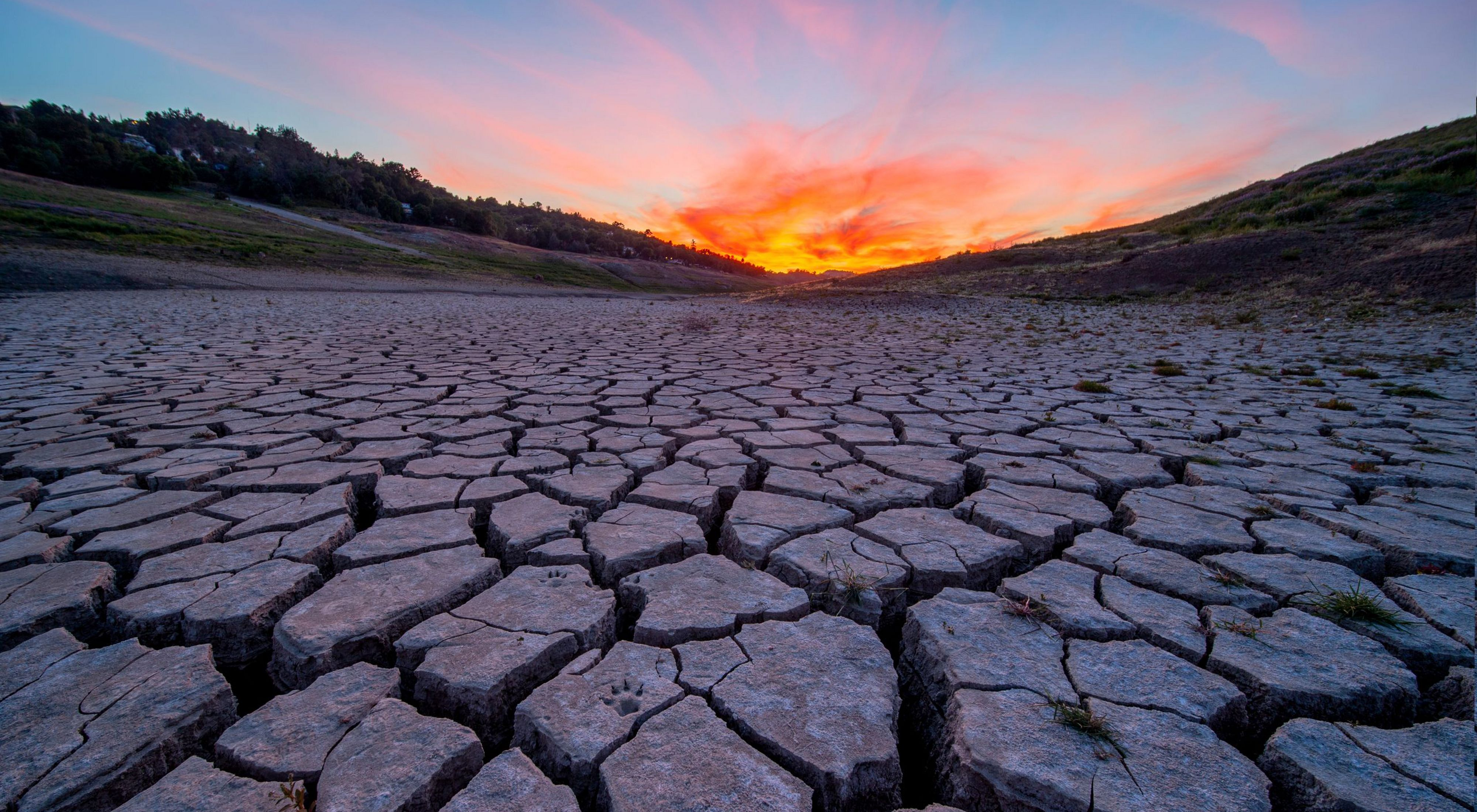 Photo of an orange sunset across a parched, cracked riverbed.