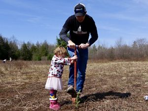 MD/DC Director of Marketing Sev Smith gets a helping hand from daughter Charleigh during red spruce planting at Cranesville Swamp Preserve.
