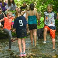 Many children play wildly in creek.
