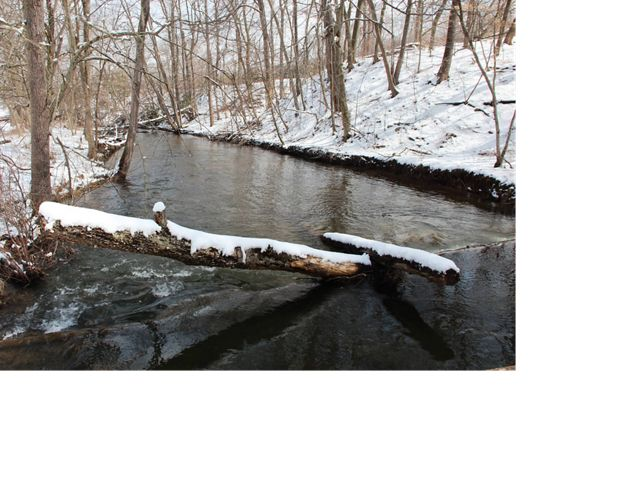 A stream flows through a snowy landscape.