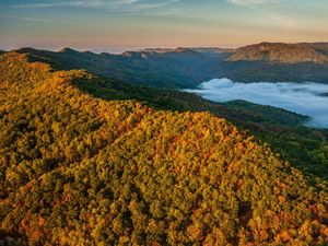 A mist emerges near a colorful forested ridge.