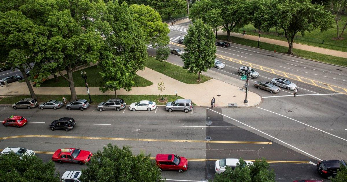An aerial view of street scene with cars at an intersection.