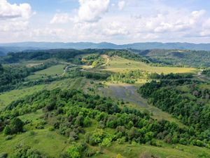 Aerial view of former mine lands in SW Virginia. A dark, bare earth scar lays in the center of an open field that is being reclaimed by grass. The patch is circled by trees and ringed by paved roads.